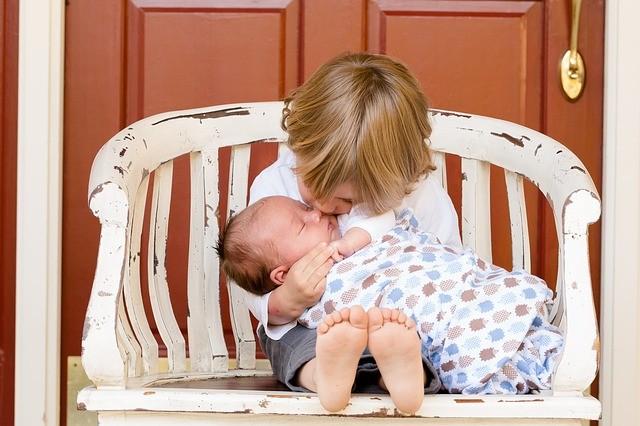 Bébé dans sa gigoteuse dans les bras de son frère